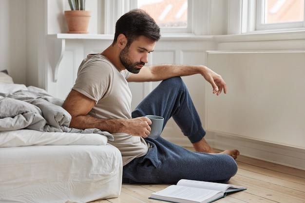 Attraktiver bärtiger kerl, der zu hause während der arbeit aufwirft