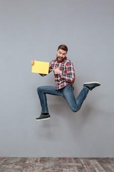 Attraktiver bärtiger mann, der leeres papier hält und springt