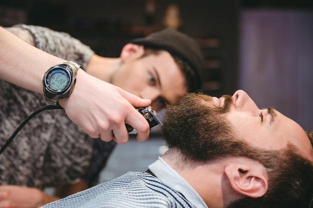 Attraktiver bärtiger mann, der seinen bart von einem modernen friseur im friseurladen rasiert