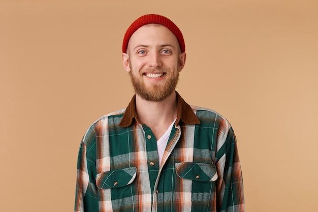 Attraktiver bärtiger mann im roten hut mit breitem lächeln, das gesunde zähne zeigt