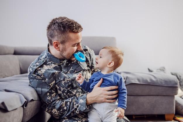 Attraktiver bärtiger soldat, der auf dem boden im wohnzimmer sitzt, seinen geliebten entzückenden jungen hält, beißring im mund hält und ihn neckt.