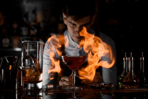 Attraktiver barmixer, der auf das feuer um das cocktailglas aufpasst