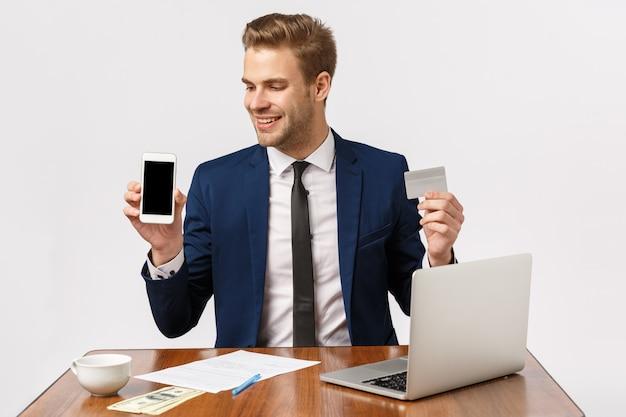 Attraktiver blonder bärtiger geschäftsmann im büro mit laptop, smartphone und kreditkarte