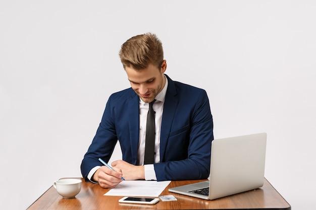 Attraktiver blonder bärtiger geschäftsmann im büro mit laptop