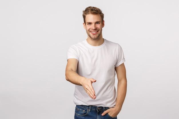 Attraktiver blonder bärtiger mann im weißen t-shirt, das handerschütterung tut