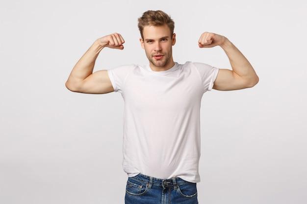Attraktiver blonder bärtiger mann im weißen t-shirt, das muskeln zeigt