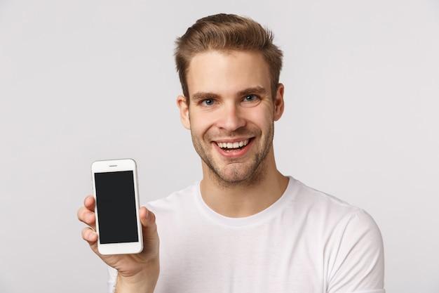 Attraktiver blonder bärtiger mann im weißen t-shirt, das smartphone zeigt
