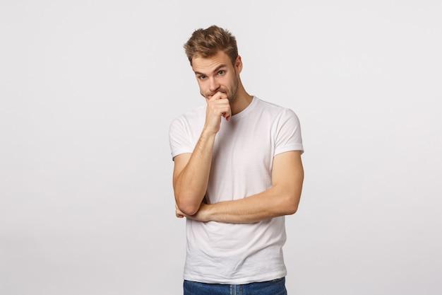 Attraktiver blonder bärtiger mann im weißen t-shirt denken