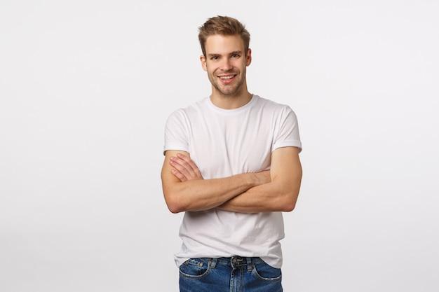 Attraktiver blonder bärtiger mann im weißen t-shirt mit den gekreuzten armen