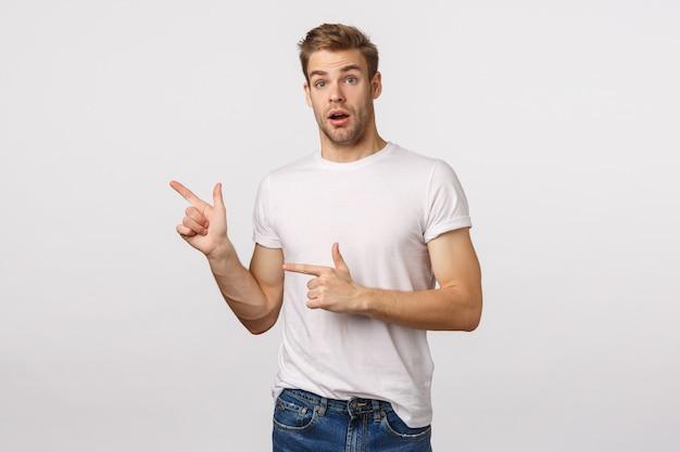 Attraktiver blonder bärtiger mann im weißen t-shirt zeigend auf die seite