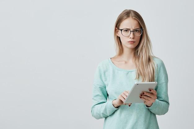 Attraktiver blonder büroangestellter in brillen arbeitet mit digitalem tablet