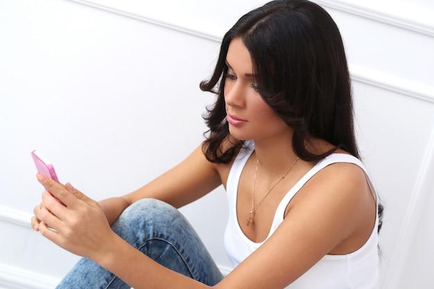 Attraktiver brunette, der auf dem boden sitzt