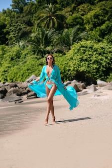 Attraktiver brunette mit einem dünnen körper und langen beinen, die in einem blauen bikini und in einem blauen kap aufwerfen, setzen auf den strand