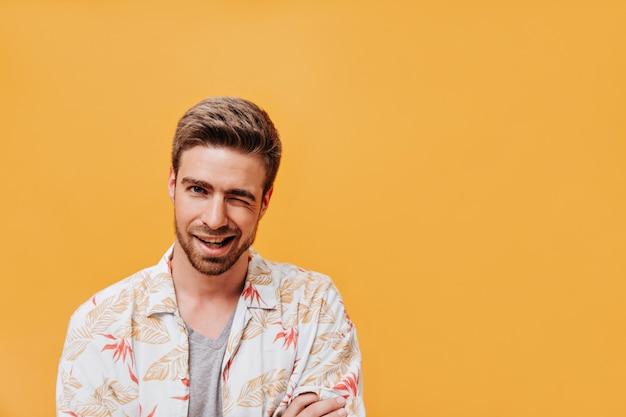 Attraktiver cooler mann mit ingwerbart in weißer modischer sommerkleidung, der auf orangefarbener isolierter wand zwinkert und lächelt