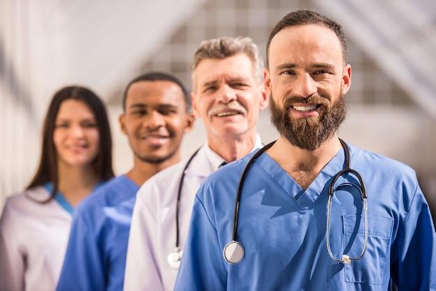 Attraktiver doktor vor medizinischer gruppe im krankenhaus.