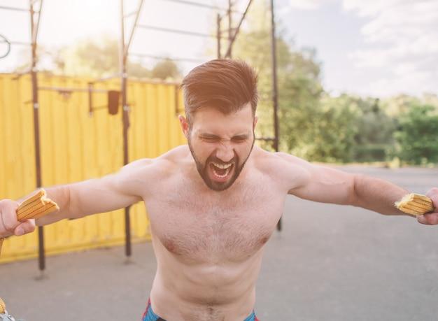 Attraktiver eignungsmann, der draußen übungen tut. sport, crossfit. im freien trainieren. muskulöser mann, der draußen ausbildet.