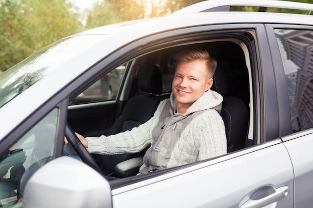 Attraktiver eleganter glücklicher mann in einem guten teuren auto