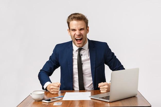 Attraktiver empörter blonder bärtiger geschäftsmann im büro mit laptop
