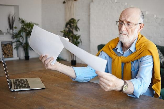 Attraktiver erfahrener sechzigjähriger buchhalter, der papiere hält, konzentriertes konzentriertes aussehen während der arbeit am finanzbericht, am schreibtisch sitzend, mit laptop. menschen, lebensstil und technologie