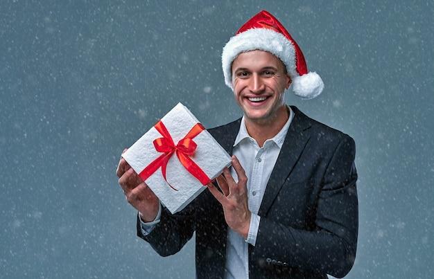 Attraktiver erfolgreicher geschäftsmann in jacke und hemd in einer mütze von santa claus mit einer geschenkbox im studio auf grauem hintergrund.