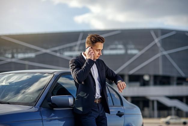 Attraktiver erfolgreicher junger geschäftsmann in einem geschäftsanzug und auf der hand, die auf smartphone in der nähe seines autos spricht