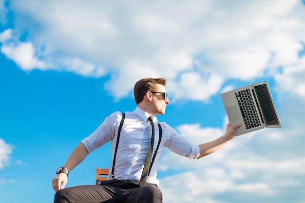 Attraktiver ernster busunessman im weißen hemd, in der bindung, in den klammern und in der sonnenbrille, die gehen, den laptop zu brechen