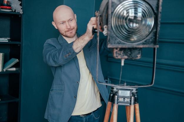 Attraktiver erwachsener kahler mann mit bart in der klage, die alte beleuchtungsvorrichtung, videolicht betrachtet