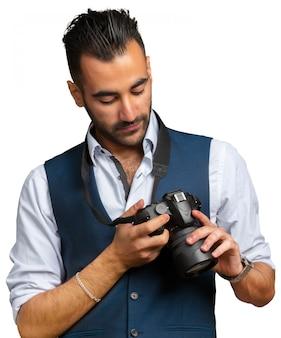Attraktiver erwachsener mann mit einer kamera getrennt auf weißem hintergrund