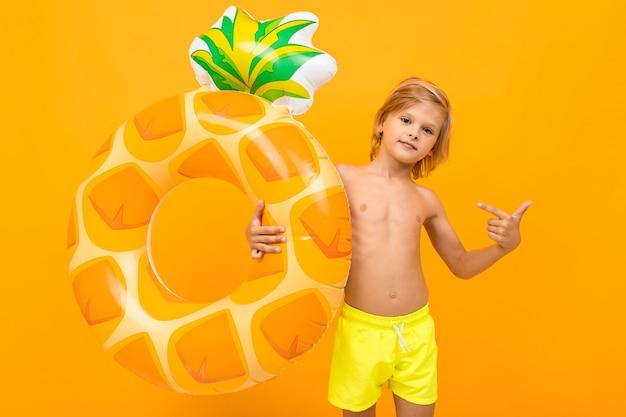 Attraktiver europäischer blonder junge in gelben badehosen mit schwimmkreisananas auf einer orange