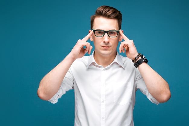 Attraktiver fälliger geschäftsmann in der kostspieligen uhr, in den schwarzen gläsern und im weißen hemd