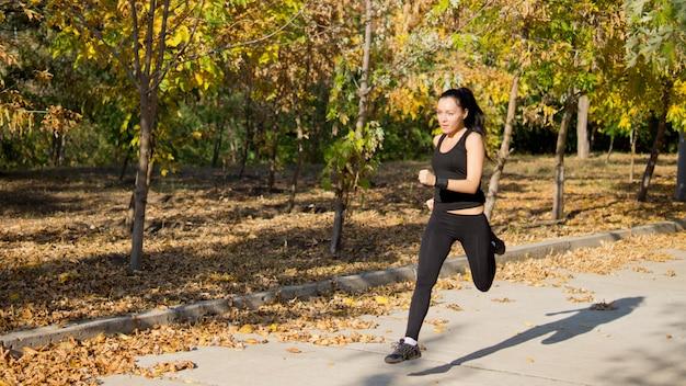 Attraktiver fit weiblicher athlet, der mit geschwindigkeit entlang einer ländlichen spur durch einen park läuft
