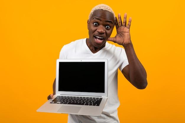 Attraktiver freudiger überraschter amerikanischer mann, der laptop mit modell hält