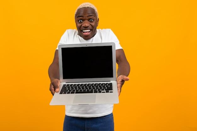 Attraktiver freudiger überraschter amerikanischer mann im weißen t-shirt hält seine hände mit laptop mit modell auf gelbem hintergrund aus