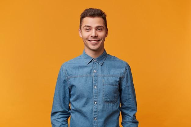 Attraktiver freundlicher niedlicher junger mann der art, der sanft lächelnd gekleidet in einem schönen jeanshemd lokalisiert auf einer gelben wand kleidet