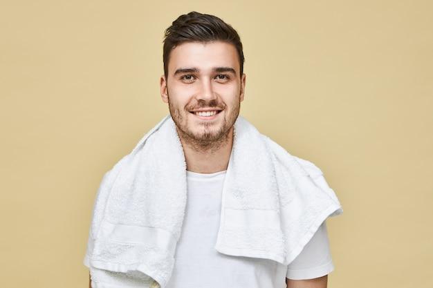 Attraktiver fröhlicher junger europäischer mann mit stoppeln und weißem handtuch um den hals, der breit lächelt und sich am morgen vor der arbeit im badezimmer das gesicht rasiert