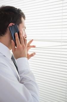 Attraktiver geschäftsmann, der durch rollo beim anrufen ausspioniert
