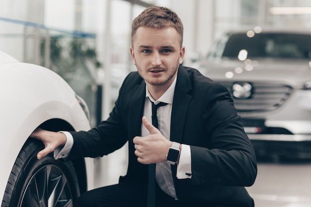 Attraktiver geschäftsmann, der neues automobil an der verkaufsstelle kauft