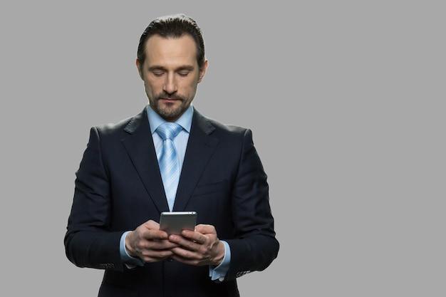 Attraktiver geschäftsmann, der smartphone auf grauem hintergrund verwendet. selbstbewusster ceo mit handy. menschen-, geschäfts- und lifestyle-konzept.