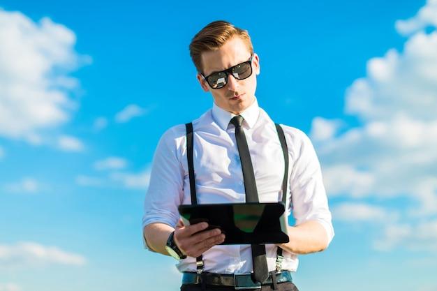 Attraktiver geschäftsmann im weißen hemd, in der krawatte, in den klammern und in der sonnenbrille schauen in der tablette