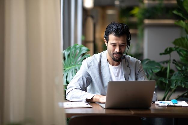 Attraktiver geschäftsmann in anzügen und kopfhörern, der beim arbeiten am desktop-computer am modernen schreibtisch lächelt. kundendienstassistent, der im büro arbeitet. voip-helpdesk-headset