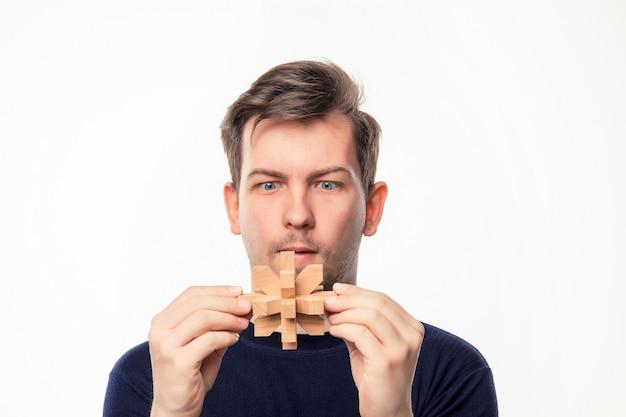 Attraktiver geschäftsmann mit 25 jährigen, der hölzernem puzzlespiel verwirrt betrachtet.