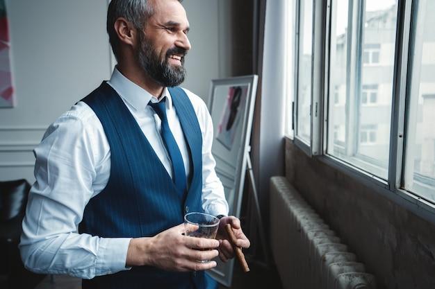 Attraktiver geschäftsmann mit einer zigarre und einem glas whisky.