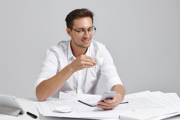 Attraktiver geschäftsmann trinkt kaffee, nachrichten mit partnern, umgeben von papieren und skizzen, liest nachrichten online, nutzt die kostenlose internetverbindung. herrlicher männlicher architekt, der bei der arbeit beschäftigt ist