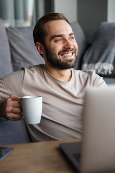 Attraktiver, glücklicher, intelligenter junger mann, der auf einem boden im wohnzimmer sitzt, an einem laptop arbeitet und kaffee trinkt