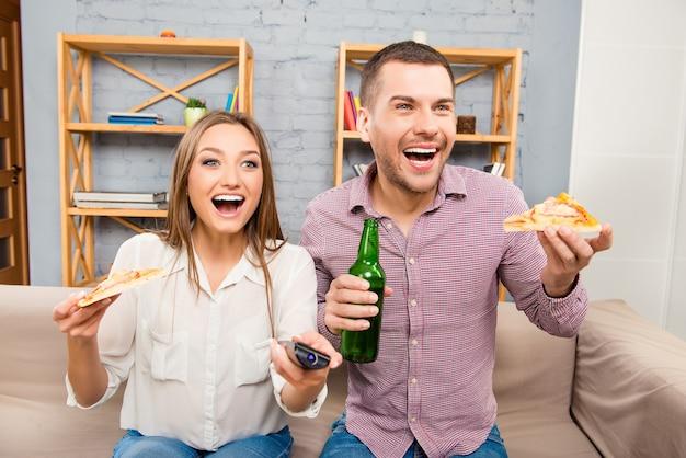 Attraktiver glücklicher junger mann und frau, die mit bier und pizza fernsehen