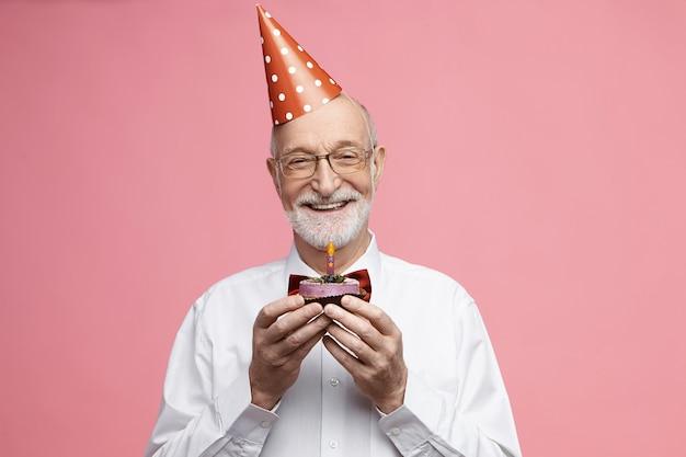 Attraktiver glücklicher pensionierter kaukasischer mann, der fliege, brille und kegelhut trägt, der seinen 80. jahrestag feiert, isoliert mit geburtstagstorte in seinen händen posiert, kerze ausblasen und wunsch machen