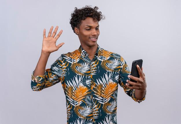 Attraktiver gut aussehender dunkelhäutiger mann mit dem lockigen haar im bedruckten blatthemd, das mit freund während des videoanrufs spricht und hand auf frontkamera des mobiltelefons winkt