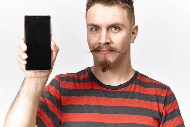 Attraktiver gut aussehender junger unrasierter europäischer mann, gekleidet in gestreiftem t-shirt, das generisches schwarzes handy mit leerem display mit copyspace für ihren text, vorlage oder werbung hält