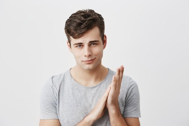 Attraktiver gutaussehender kaukasischer mann mit ansprechendem aussehen, trägt ein graues t-shirt, hält die hände zusammen, sieht nachdenklich aus, stellt sich etwas angenehmes vor und plant, wie man wochenenden verbringt