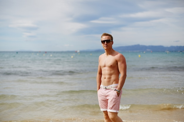 Attraktiver hemdloser athletischer junger mann am strand am meer. junger muskulöser mann mit perfektem körper in shorts und sonnenbrille, die durch die seeküste gehen. reisemode. sportlicher lebensstil
